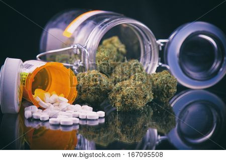 Detail of cannabis buds and prescriptions pills over reflective surface - medical marijuana dispensary concept