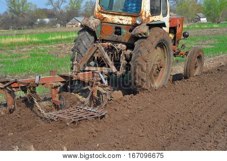 Plowing field with old rustic village tractor.