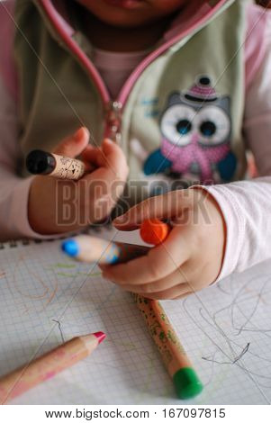 Child hands holding different color crayons close up