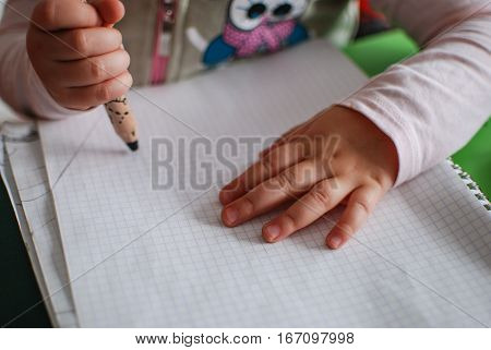 Child's hand while drawing with crayons on a piece of paper