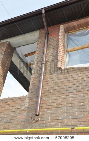 Rain Gutter System  Downspout Pipe Installation on House Construction Wall