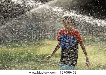 Children play with jets of water in hot weather