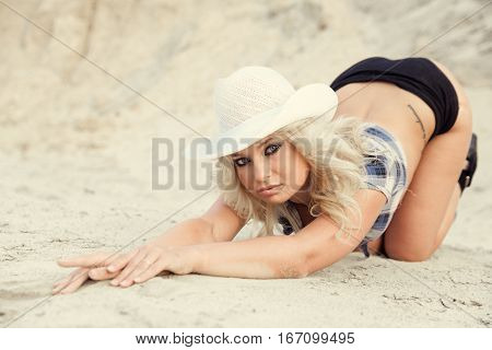 Beautiful Caucasian woman kneeling on the sand