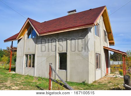 Plastering Exterior House Wall Ready for Painting. Facade Thermal Insulation and Painting Works During Exterior Renovations. Roofing Construction with Asphalt Shingles Installation Exterior.