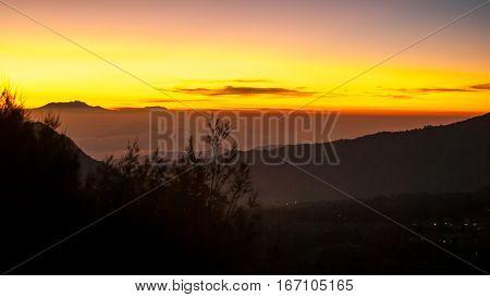 Sunrise at volcano Mount Bromo, sun beyound horizon, clouds swimming around