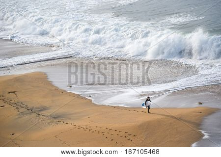 TORQUAY AUSTRALIA - JULY 20 2016 :surfer man walk on the beach near white water wave in the sea at Bells beach.