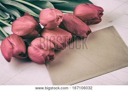 Red tulips with paper sheet. Vintage style retro still life