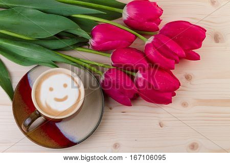 Coffee and red tulips on wooden background Top view
