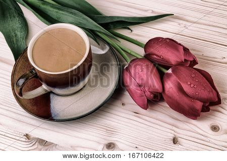 Cup of coffee with tulips.Vintage still life