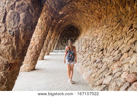 Young girl tourist with a backpack walking through the colonnade in Park Guell by architect Antoni Gaudi. Barcelona Spain.