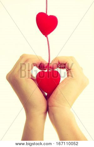 Love and help. Smoothy female hands with sign symbol of charity and fondness. Palm with red little hearts.