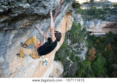 Extreme sport. Young man climbing a rock with belay. Adventure lifestyle. Freedome.