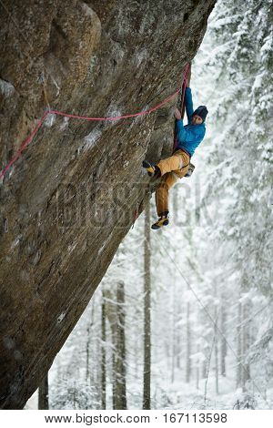 Extreme winter sport. Young man climbing a rock with belay. Rope climbing.