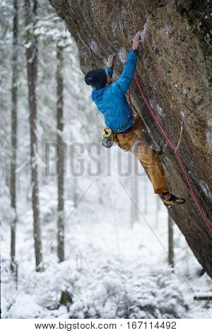 Rock climber on a challenging ascent. Extreme climbing. Unique winter sports. Scandinavian nature