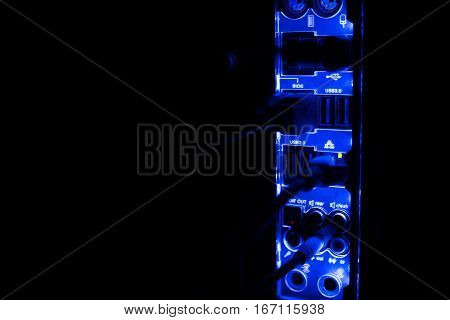 Blackout, blurred borders. Close up of blue network cables connected to black switch glowing in the dark.