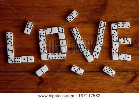 Love sign of white domino pieces on bright brown wooden background (bithday, valentines day, wedding)