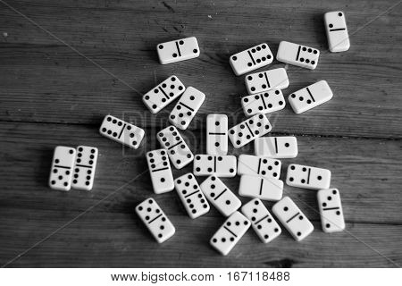 Domino game pieces texture close up on wooden table in black and white style