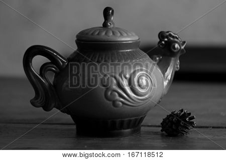 Beautiful clay teapot rooster close up on textured background in vintage black and white style