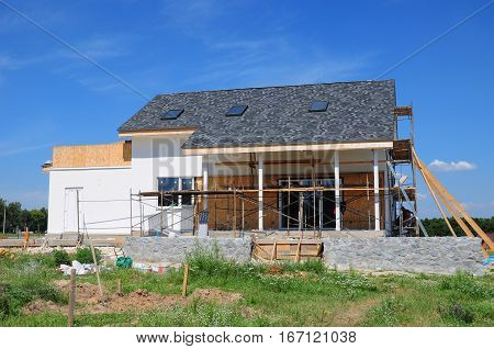 Home Renovation Remodeling Insulation and Repair Outdoor. Renovating a House. House Construction with Terrace Asphalt Shingles Roof and Skylights.