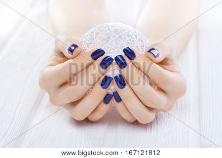 blue manicure with a white ball of yarn on the white wooden table.