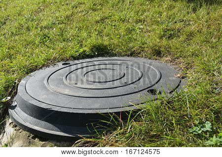Manhole cover in the garden. Plastic Manhole cover.