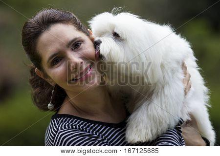 Happy brunette woman holds white maltese dog on a garden background