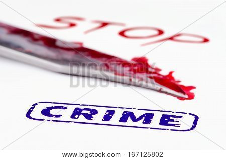Macro shot of stamp crime on a white paper. Knife and stop written in blood.