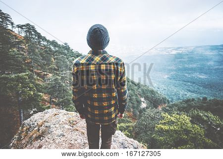 Man Traveler standing on cliff alone aerial view forest mountains on background Travel Fashion Lifestyle adventure vacations concept