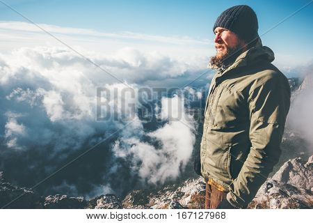 Man Traveler on mountain summit with clouds around Travel Lifestyle success concept adventure survival vacations outdoor