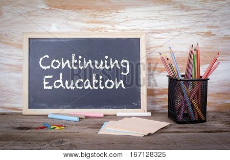 Continuing Education text on a blackboard. Old wooden table with texture.