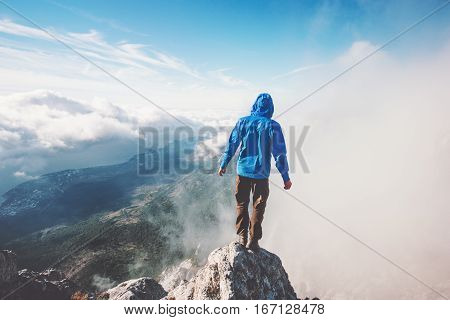 Man Traveler on mountain cliff enjoying aerial view over clouds Travel Lifestyle success concept adventure active vacations outdoor freedom emotions