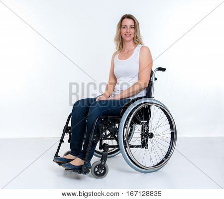 young disabled woman in wheelchair infront of white background