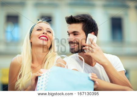 Couple sitting on the bench after the shooping man makes a telephone call girl laughing
