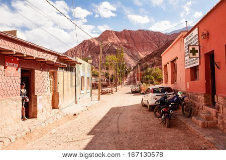Purmamarca Argentina - November 1 2016: Street in Purmamarca with indigen woman and car (Argentina)