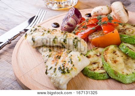 Chicken breast with grilled vegetables on a wooden board