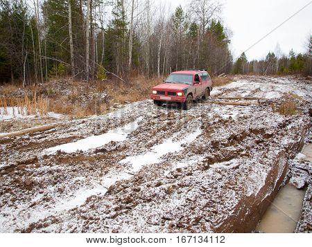 NIZHNY TAGIL. RUSSIA - JUNE 12 2013: Broken logging road in the heart of Siberia. Red offroad car overcomes winter thaw