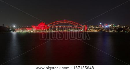 28 January 2017 - Sydney harbour skyline with North Sydney, Harbour Bridge and Opera House lit up for the celebration of the Lunar New Year - Year of the Rooster in Chinese Horoscope