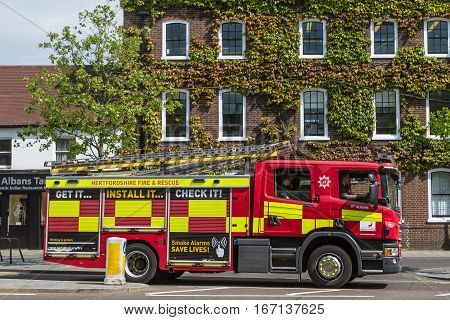ST ALBANS UK - JUNE 6 2016: A fire truck drives through St Peters Street past an ivy clad building