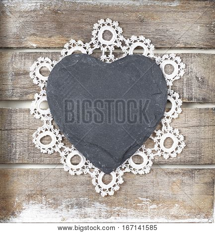 Stone heart and lace on wooden background