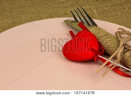 Cutlery wrapped in woven napkin on a brigh pink plate and red heart. Close horizontal view