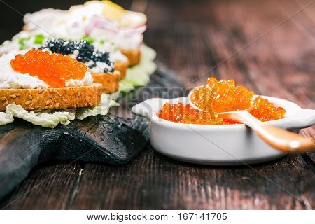 Salmon roe sandwiches with farmer cheese on wood