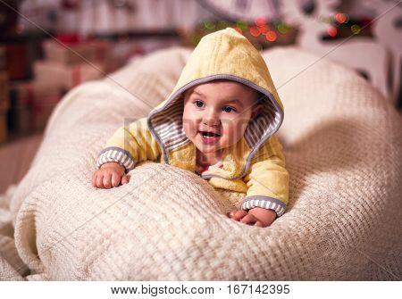 Small baby girl on yellow sheepskin bathrobe