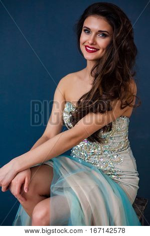 Beautiful woman wearing sparkling evening dress. Professional make-up and hairstyle. Perfect skin. Fashion photo. Natural beauty.