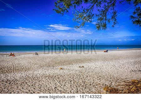 Anna Maria Island, FL, USA - December 2: People sit on the deserted Anna Maria Island beach in Florida