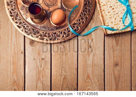 Jewish holiday Passover concept with matzah seder plate egg and wine on wooden background. View from above