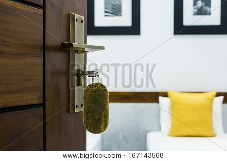 Close-up photography of key in keyhole of modern door leading to hotel room
