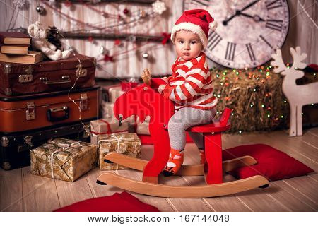 Baby In Santa Hat And Christmas Costume On Rocking Deer. Beautiful Little Baby Celebrates New Year's