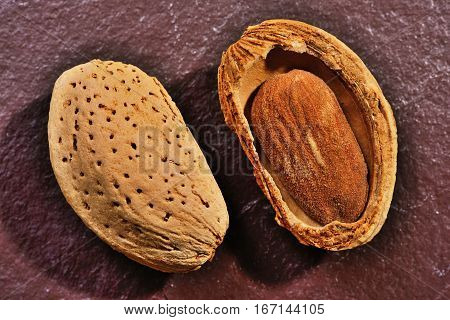 Almonds on stone background Almond nut in shell and shelled close up