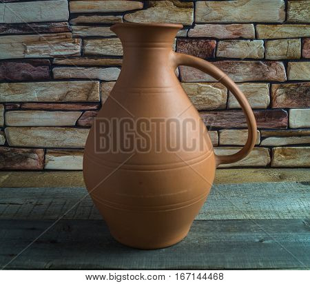 Elegant earthenware jug on a wooden table.