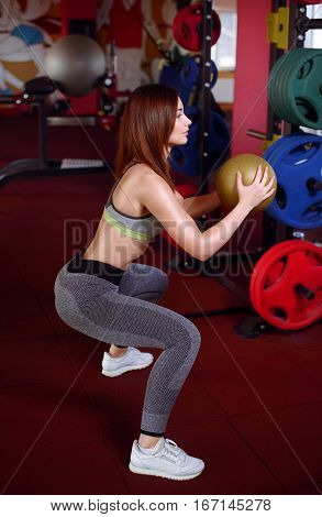 Athlete Crouched Doing Wall Balls Exercises At The Gym